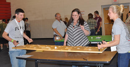Volunteer Mary Reynolds watches as Dustin Morgan and Cynthia Frank tilt a labyrinth board to guide a golf ball to the end of the maze at TCHS Project Graduation on May 24.