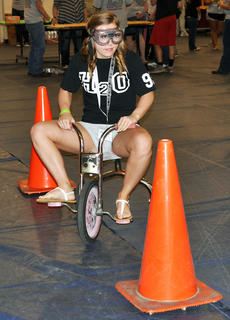 McKenzie Lawson pedals her tricycle between cones while wearing alcohol simulation goggles at TCHS Project Graduation on May 24.