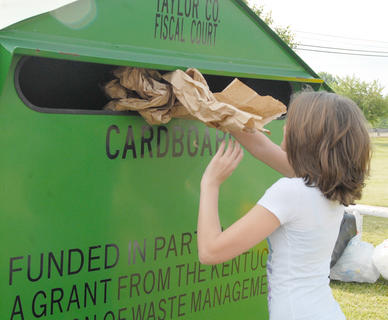 Taylor County Conservation District hosted a Recycling Day on Saturday, April 28, to encourage residents to recycle. Those who recycled received a free recycling container and two trees from the state's Division of Forestry. Above, Kimberly Harden of Campbellsville recycles some cardboard.
