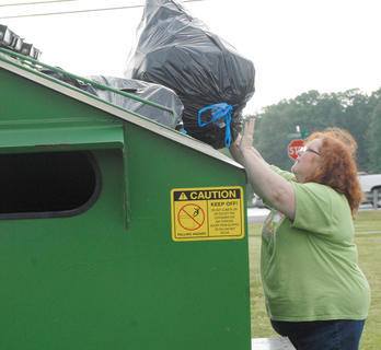 Taylor County Conservation District hosted a Recycling Day on Saturday, April 28, to encourage residents to recycle. Those who recycled received a free recycling container and two trees from the state's Division of Forestry. Above, Linda Russell of the Taylor County Conservation District puts some recyclables into one of several bins that are placed throughout Taylor County.