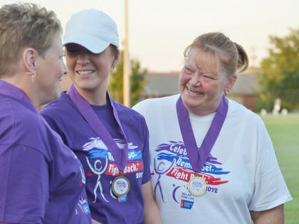 Cancer survivors smile together after they greet the crowd.