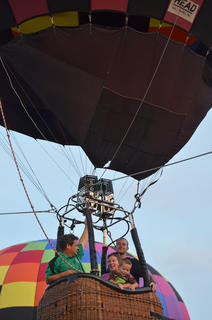 Stephanie and Kenton Gibson take their children for a ride in a hot air balloon ride. At left is pilot Tom Steinbock of Crestwood.