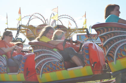 Teenagers and adults alike enjoy riding the midway rides, like this children&#039;s roller coaster, at the fair.