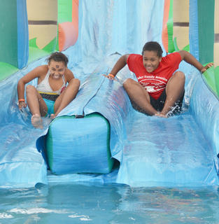 Shay Williams, at left, and Kayla Young, of Campbellsville, smile as they prepare to get wet on a slide at the Family Fun Zone.
