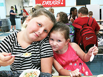 Fourth-grader Alyssa Smothers has breakfast with her younger sister Melina on the first day of school at Taylor County Elementary School.