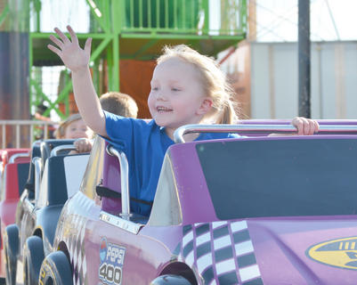 Addison Banks of Paris waves to her mother as she rides the Speedway ride.