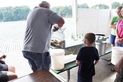 Dakota Morgan, 6, anxiously waits to learn the total weight of his fishing success Saturday morning at City Lake.