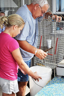 Savanna Sharp, 11, watches as Roger Stiles weighs her catch at the City Lake kids' bluegill tournament.