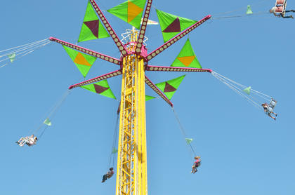 Children, teenagers and adults fly high in the air on the swings.