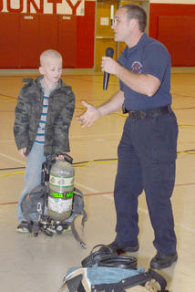 Campbellsville Fire & Rescue Engineer Keith Bricken, who coordinates fire prevention activities, shows Taylor County Elementary School second-grade student Dakota Swarts that firefighting equipment can be very heavy.