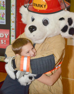 TCES second-grader Matthew Sampley hugs Sparky, Campbellsville Fire & Rescue's fire dog, after learning about fire prevention.