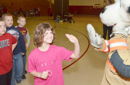 TCES second-grader Abby Willis gives Sparky, Campbellsville Fire & Rescue's fire dog, a high five.