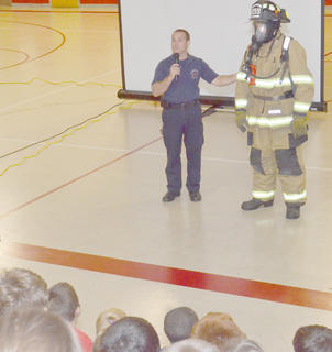 Campbellsville Fire & Rescue Engineer Keith Bricken, who coordinates fire prevention activities, shows second-grade students at Taylor County Elementary School that firefighters, like Kevin Pike, are their friends and will only come into people's homes to help them.