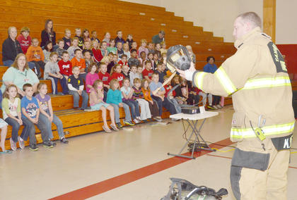 Firefighter Kevin Pike shows students the parts of his uniform.