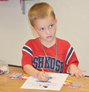 Kindergartener Aiden Willis colors before school starts.
