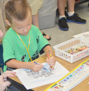 Kindergartener Kayden Durham colors with a handful of crayons.