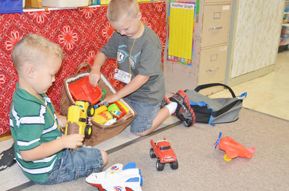 Tyler Phillips, at left, and Alex Matthews find toys to play with before their kindergarten class begins.Staff members and parents help students go through the breakfast line.