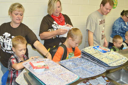 Staff members and parents help students go through the breakfast line.