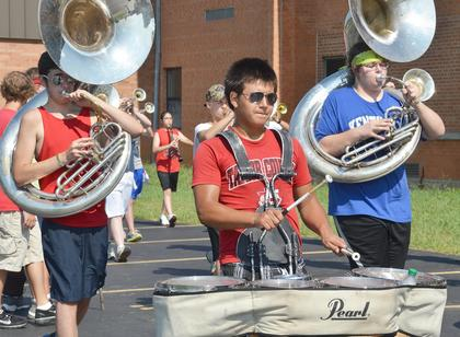 From left, TCHS marching band members Dalton Bennett, Anthony Gonzalez and Jacob Gray play during a drill at camp on Tuesday.