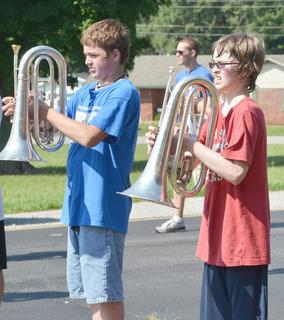 TCHS baritone players Jacob Vaughn, at left, and William Schultz squint in the sun as they perform a drill at band camp on Tuesday.