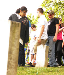 Students look at graves at the Confederate cemetery near Tebbs Bend Battlefield on Friday, April 20.