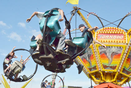 Fairgoers raise their hands as they ride the Tornado.