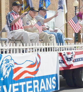 Veterans wave to the crowd during the parade.