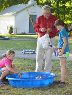 John Hall, pastor at Stoner Creek United Methodist Church, helps children play games during youth night.