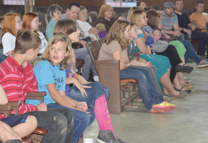 Children listen as Christian comedian Greg Strange of Nashville, Tenn., tells them a joke during youth night.