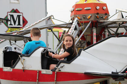 Alexis Roddy smiles while she and her brother Isaac fly a tyke-sized airplane.