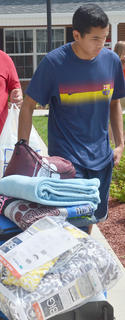 Matthew Malabanan of Hopkinsville carries clothing to his sister Jessica's dorm room.