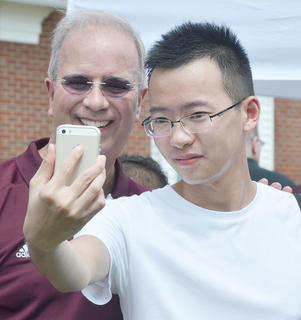 Wu Wang, an exchange student from China, takes a photo of himself with CU President Dr. Michael Carter at an ice cream social on Saturday afternoon.
