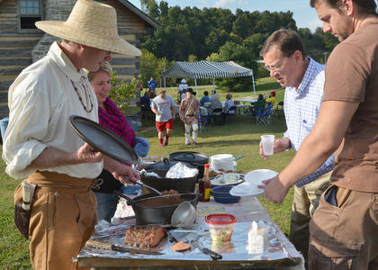 Dr. Richie Kessler and Suzanne Ince, who is a guide at the nature area at Tebbs Bend and lives at the Tollgate House, both at left, serve food to Billy B. Smith, third from left, and Robert Wilson, at right, of Campbellsville.