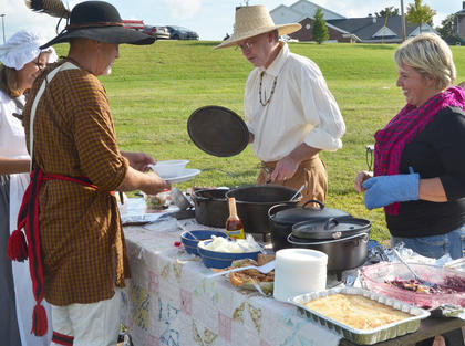 Dr. Richie Kessler and Suzanne Ince, who is a guide at the nature area at Tebbs Bend and lives at the Tollgate House, serve food to Connie and Frank Hansford.
