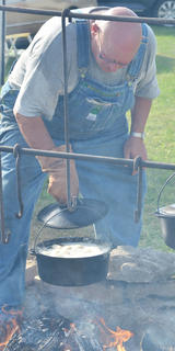 Dale Houk cooks potatoes in an iron kettle.