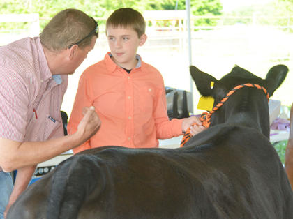 Hunter Miller receives advice from a judge at the fair's beef show.