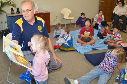 """Gathered together on a pile of blankets and pillows, the children listen intently as they hear about dancing giraffes, how to care for horses, and what it would be like if all animals lived indoors. Taylor County Public Library hosted Books for Breakfast last Saturday, with local """"celebrities"""" reading to the 140 children who attended. There was also face painting, crafts, free breakfast and an appearance by T'Alli and Guessey, horses owned by Tom and Marnie Braun of Campbellsville. Above, Children listen as Campbellsville Mayor Tony Young reads a book to them."""