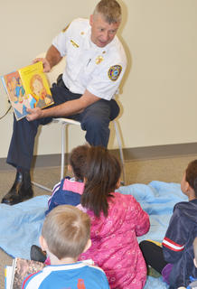 Children listen as Campbellsville Fire & Rescue Chief Kyle Smith reads a book to them.