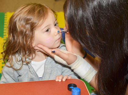 Keeley Lawler, 2, of Campbellsville, gets her cheeks and nose painted by Campbellsville High School Beta student Rosa Garcia.