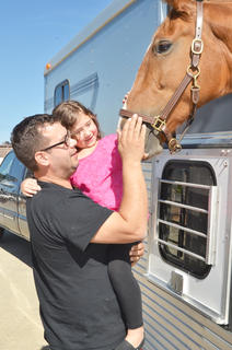 Luke Lawler of Campbellsville holds his daughter, Ivy, 6, as they pet T'Alli, an Irish Warmblood horse.