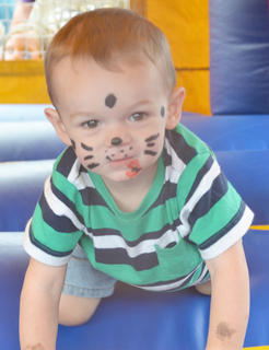 Lucian Cruse, 1 1/2, of Campbellsville, smiles as he bounces in an inflatable house at the Family Fun Zone.