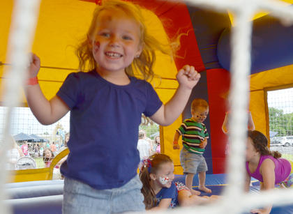 Aubri Dobson, 3, of Campbellsville, smiles as she bounces in an inflatable house at the Family Fun Zone.