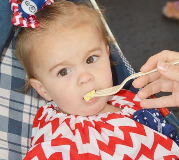 Savannah Coomer, 16 months, of Campbellsville, takes a bite of an egg at the free breakfast at Campbellsville Christian Church on Friday morning.