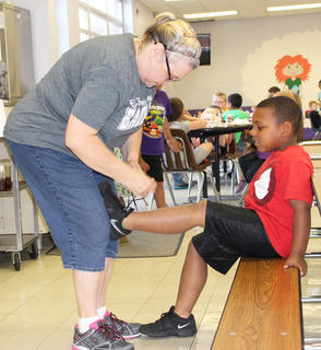 Anita Haulk, assistant manager of CES cafeteria, shows a cafeteria employee's responsibilities extend beyond the kitchen as she ties Malikah Spurling's shoe.