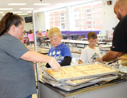 Campbellsville Elementary School cafeteria employees Rebecca Walker and Aaron Webb serve pizza to Simon Wilkerson, left, and Rowan Petett.