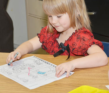 CES kindergartener Arya Stotler colors a snow picture.