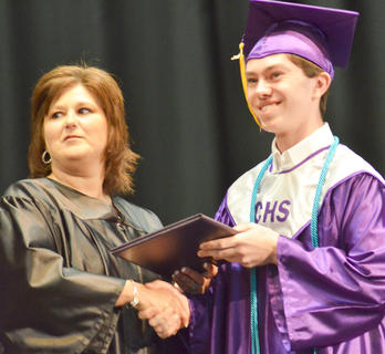 Ethan Cox smiles as he receives his diploma from Campbellsville Board of Education Chair Suzanne Wilson.