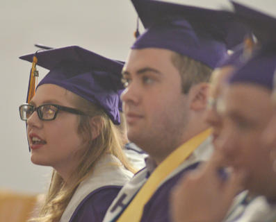 Destiny Atkinson, at left, and Ethan Bailey listen to valedictorian Emily Haley's speech.