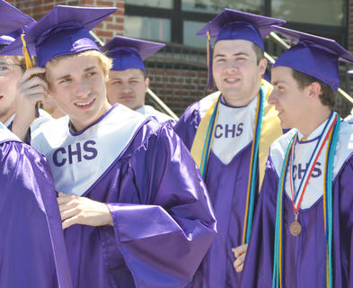 Gavin Bell adjusts his tassel as he walks with his classmates to line up for the start of Saturday's ceremony.
