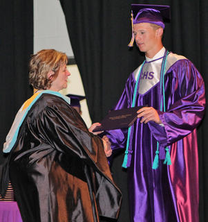 Campbellsville Board of Education Vice Chair Angie Johnson hands a diploma to graduate Grant Adams.